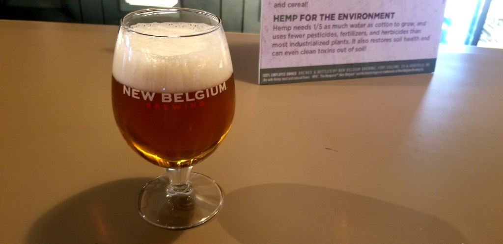 A foamy glass of hemp beer rests on a bar top