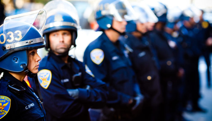 Threat modeling helps activists anticipate and respond to police repression. A line of SFPD officers in riot gear block Occupy SF Protesters after clearing them from Market Street in San Francisco.