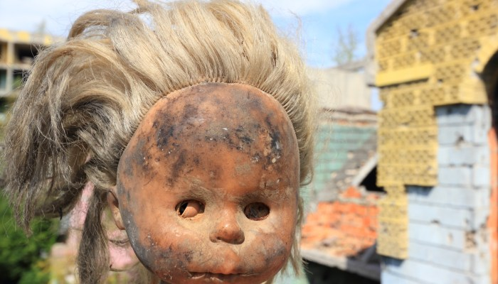 A broken, abandoned doll with blonde hair covered in dirt with a broken face in the ruins of Bosnia.