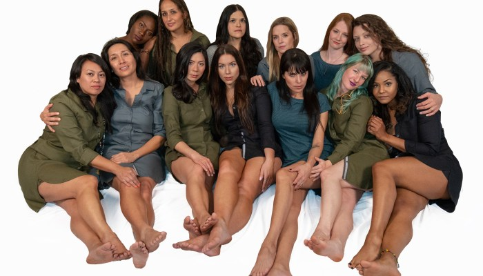 Diverse women gathered together seated wearing simple hemp dresses.