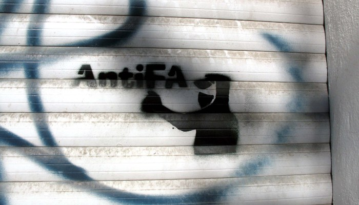 Kit went on TV to defend antifa. Photo: Graffiti on a warehouse door shows a masked black bloc protester and the word AntiFa.