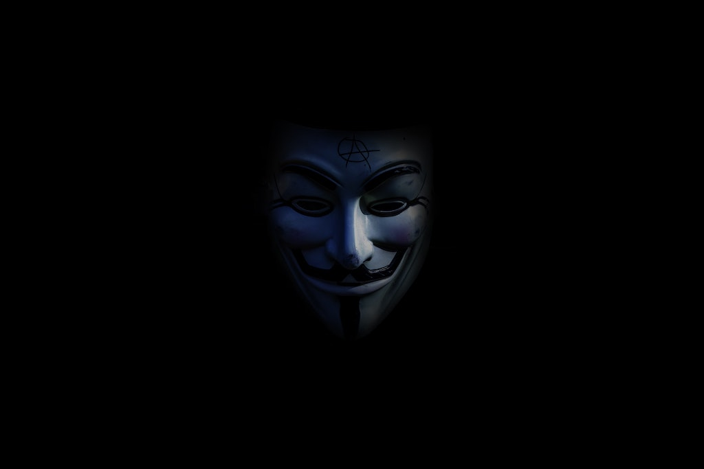"A Guy Fawkes 'Anonymous' mask looms out of a dark space. ""It Came From Something Awful"" detals 4chan, Anonymous, the rise of QAnon and what the author sees as a grand culture war."