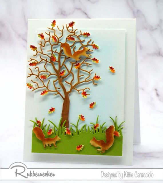 Several card making details shown on a autumn card with dimensional leaves, a popped up layer and hand colored squirrels