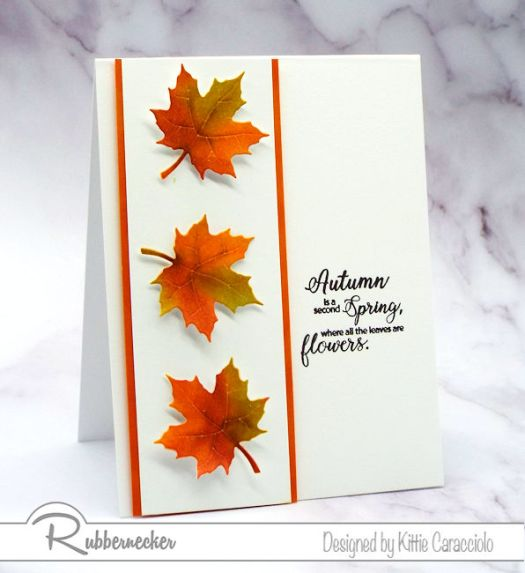 Three vibrant paper maple leaves handmade for this greeting card using inking techniques
