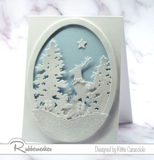 A white on white Christmas card idea with white sparkly paper die cuts arranged in a die cut oval
