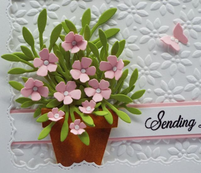 These tiny paper flowers in a tiny paper flowerpot on the front of this handmade card are adorable on their own but set against this embossed background make them stand out