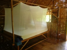 Inside of our bungalow, bed draped in a mosquito net.