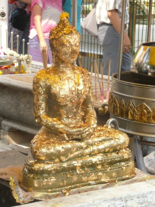 Buddah statue covered in gold leaf - part of a religious ritual