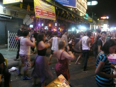 Lady boys and tourists dancing to Gangham Style in the street