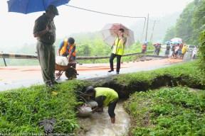 KIULU 15 Januari 2014.ADUN N11 Kiulu, Datuk Joniston Bangkuai (kiri) memerhatikan dua pekerja kontraktor penyelenggaraan jalan memasang plastik penahan air di lokasi KM6.1 Jalan Tamparuli - Kiulu, jalan yang ditutup berikutan kejadian tanah runtuh akibat hujan lebat yang berterusan lebih 12 jam yang lepas.