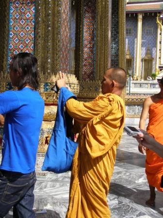 monk takes photos at the Grand Palace in Bangkok