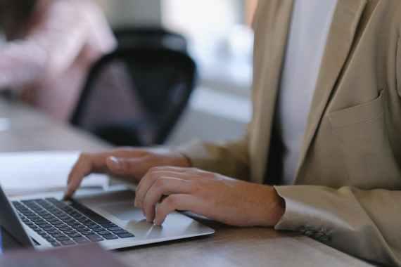 crop man typing on laptop