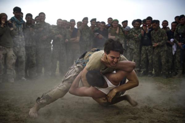 En svensk soldat besegrar en afghansk soldat under en vänskaplig (men prestigefylld) brottningsmatch mellan förbanden i Afghanistan. Trots att användandet av våld är en naturlig del av krigets natur finns i viss mån närmast en beröringsskräck för frågor om våld och dödande inom delar av den militära organisationen. Foto: Johan Lundahl, Combat Camera / Försvarsmakten