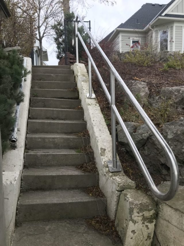 """stainless steel 2"""" railing on concrete stairway"""