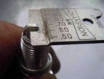 Prüfung des Elektrodenabstands bei einer neuen Zündkerze (Soll 0,7 mm)