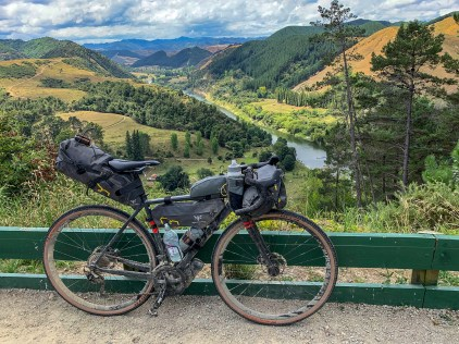 Gravel bike in the foreground, overlooking a river valley, covered in forest and grass land