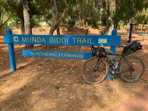 Gravel bike leaning against the Munda Biddi trailhead sign