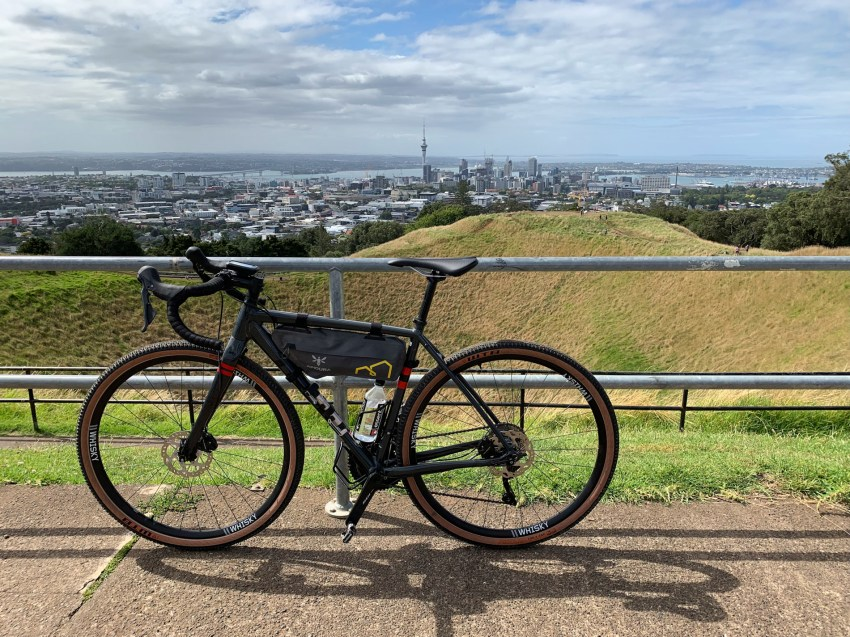 Elevated view from a hill towards Auckland downtown, with skyscrapers visible in the distance. Gravel bike leaning against railing in the foreground