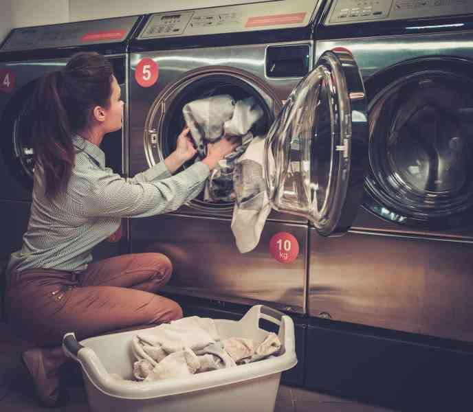 beautiful-woman-doing-laundry-at-laundromat-shop-PG9Q2JT (1) (1)
