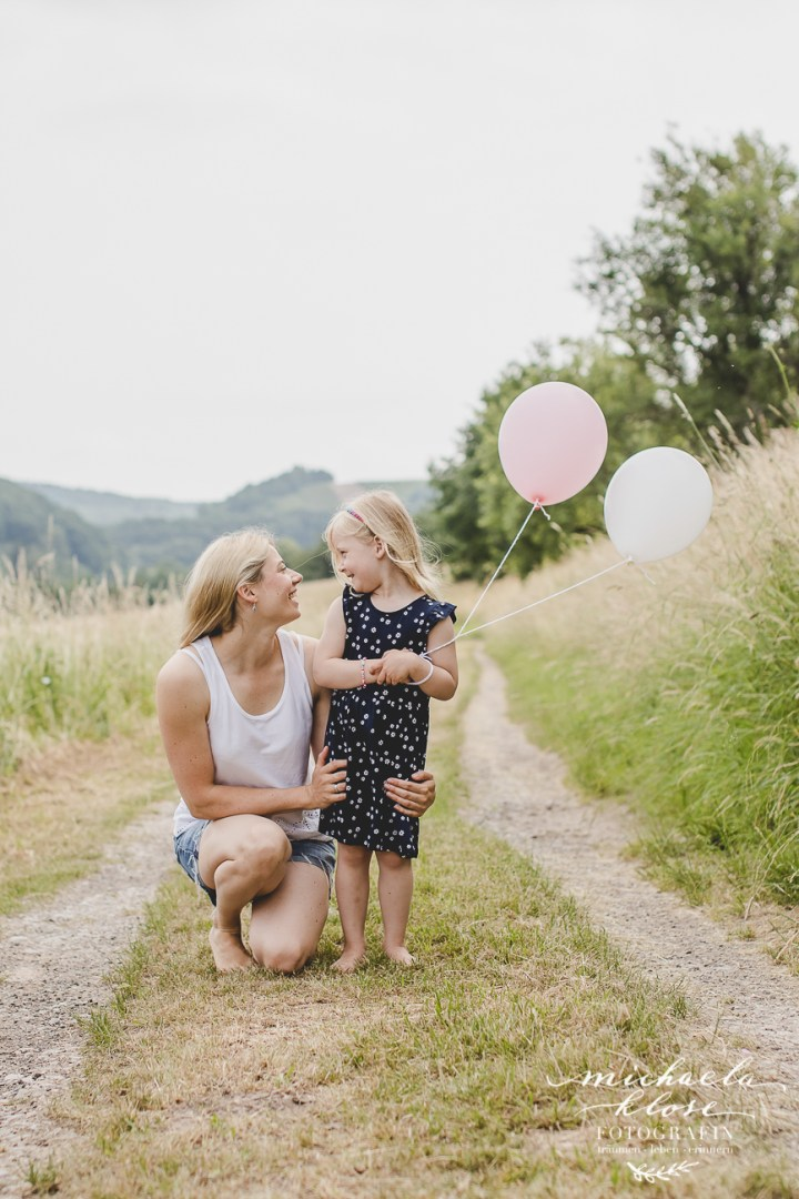 Kinderfotografin Michaela Klose Shooting Outdoor im Grünen Ballons Rosa Weiß Feldweg Mama Tochter Sohn zwei Kinder Fotografin