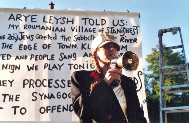 Image of Jenny Romaine with a megaphone in front of a banner that describes the history of the Backwards March.