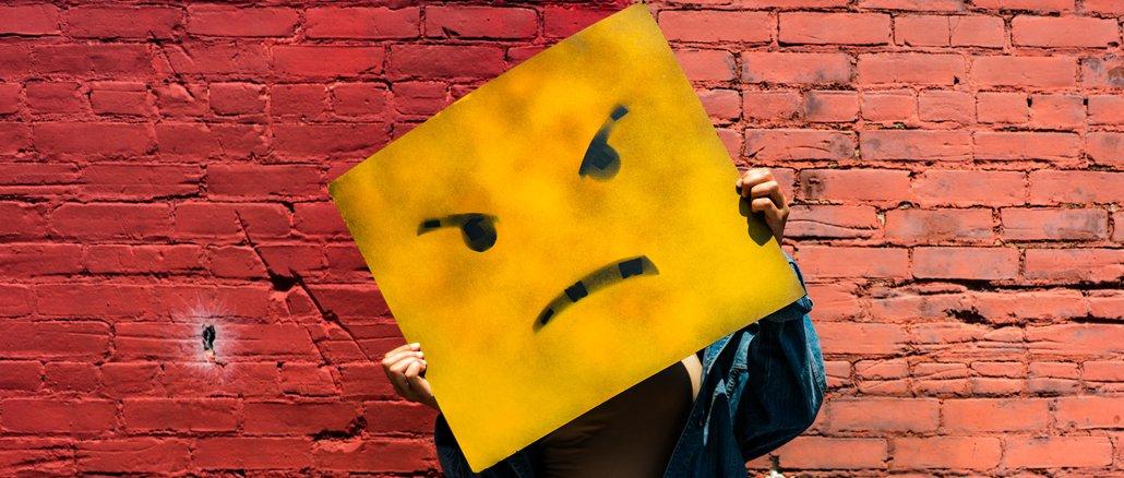 Wütend! Gelbes Quadrat mit zornigem Gesicht vor roter Ziegelwand