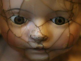 zerbrochenes Gesicht einer alten Puppe