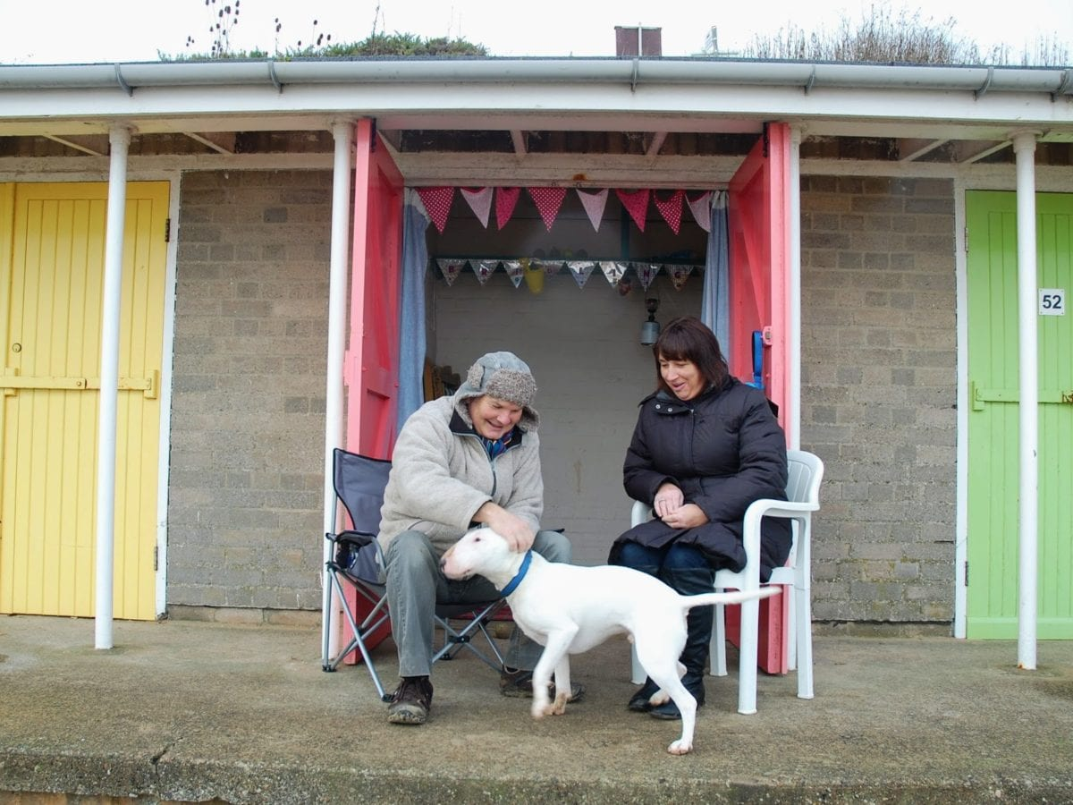 A couple and their dog outside their beach hut