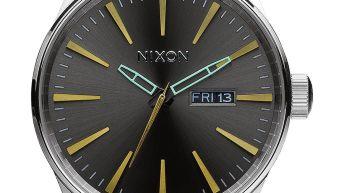 Caratula reloj Nixon en color plateado con el dial negro con detalles dorados