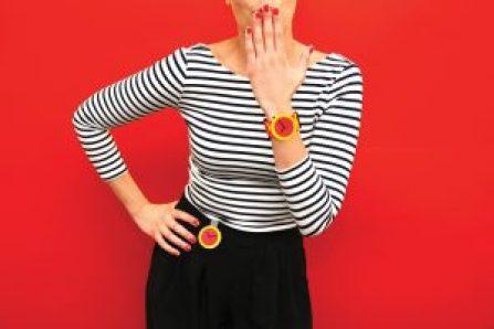 Mujer con blusa rayada, falda negra, reloj en el brazo y fondo rojo
