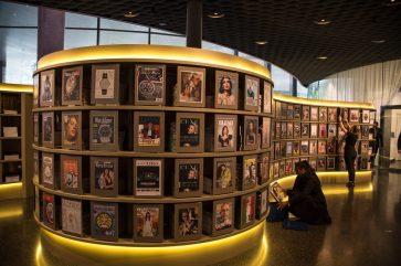 Mujer sentada en el piso observando las imagenes de la galeria en Baselworld