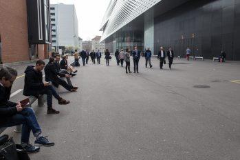 Personas sentadas en una banqueta esperando