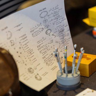 Hoja blanca con anotaciones sobre una mesa con algunos instrumentos