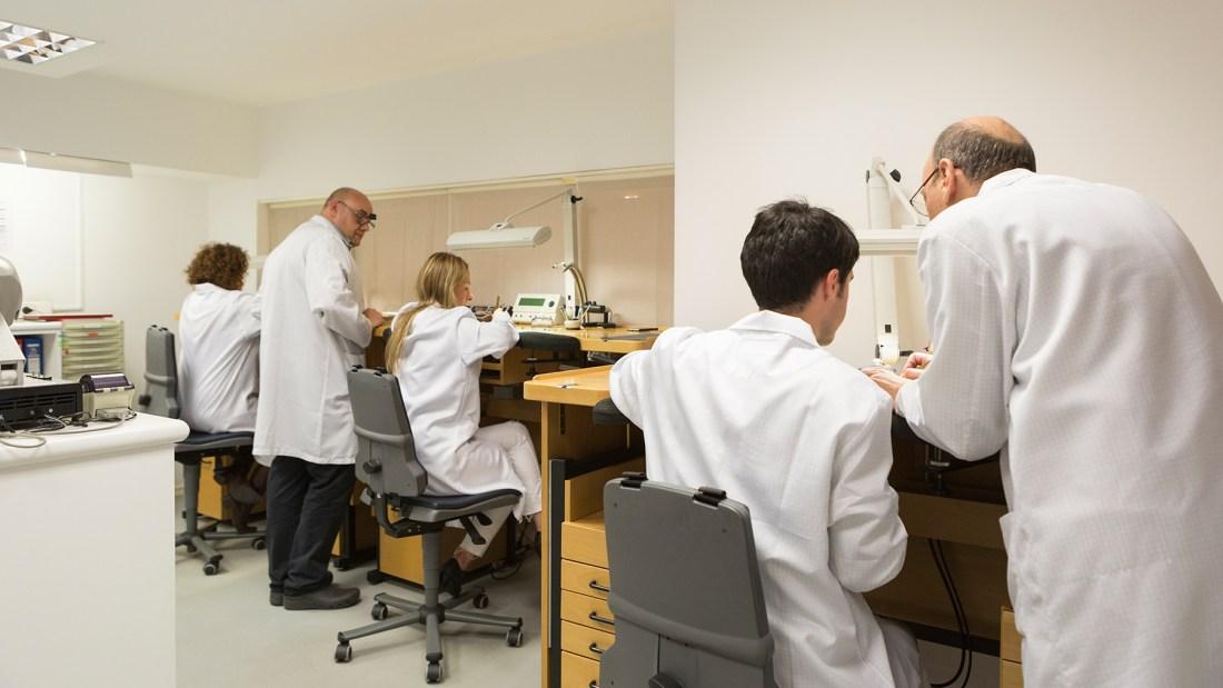 Hombres y mujeres con bata blanca en una oficina componiendo relojes