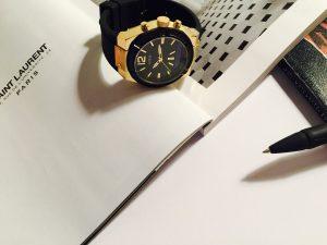 Reloj Guess con correas negras y caratula dorada sobre las paginas de un libro