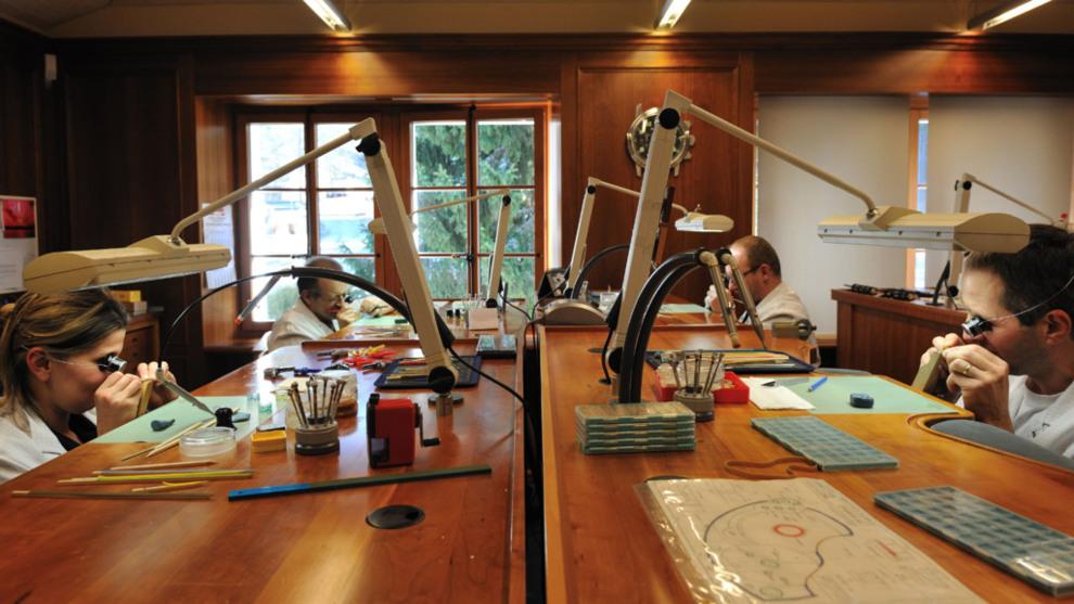 Relojeros sentados frente a una mesa de madera con instrumentos para componer relojes