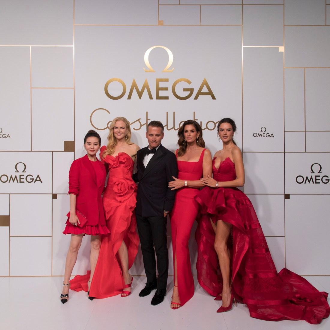 Modelos de OMEGA con vestido rojo de omega con letras doradas y fondo blanco
