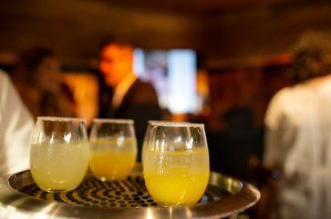 Bebidas de color amarillo en pequeños vasos de cristal sobre una charola