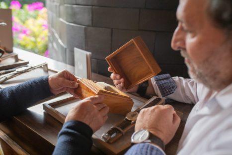 Personas observando y tomando el estuche de madera del reloj