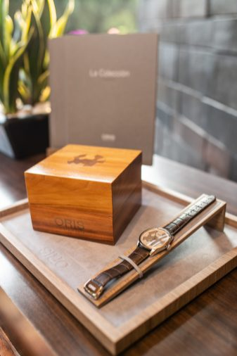 Estuche de madera a lado del reloj Oris Artix sobre una plataforma de madera