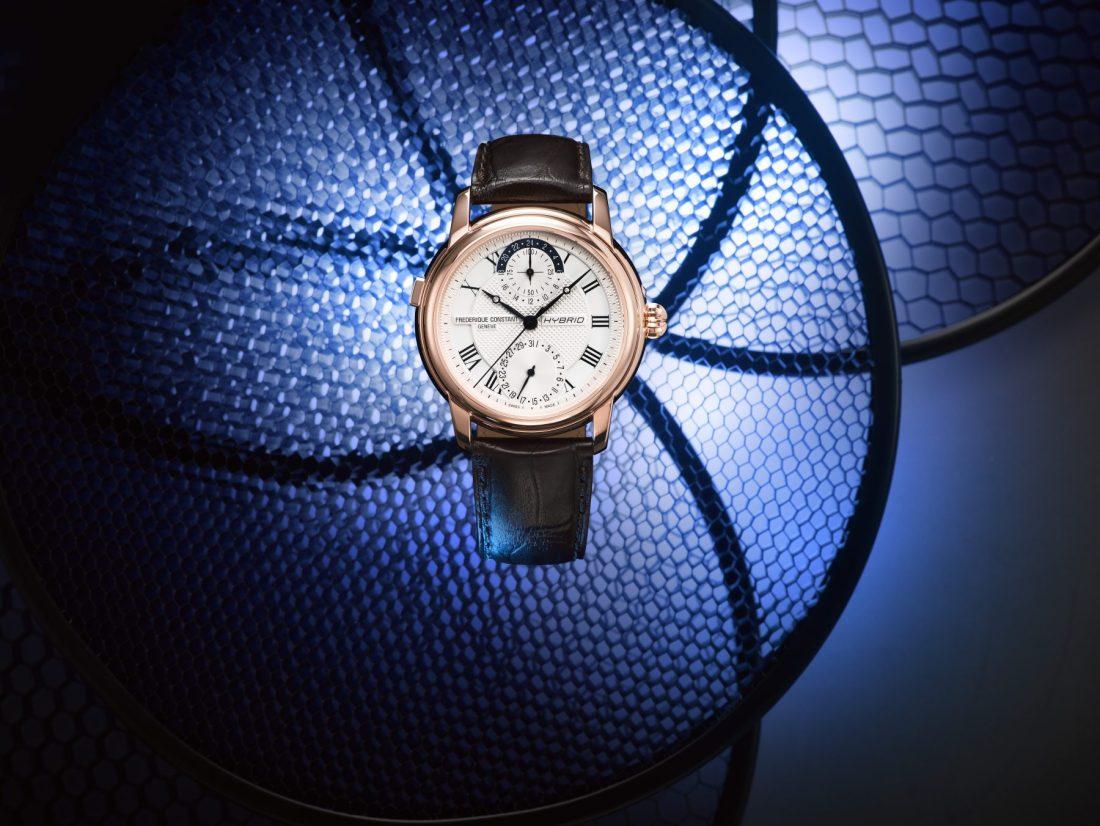 Reloj Frédérique Constant en color cafe con detalles en dorado y blanco con fondo azul
