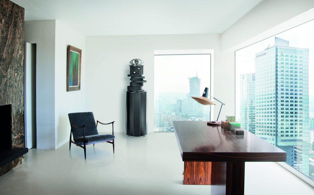 Home Office en color blanco con mesa de madera una silla en color azul marino una caja fuerte para relojes en color gris y ventanas