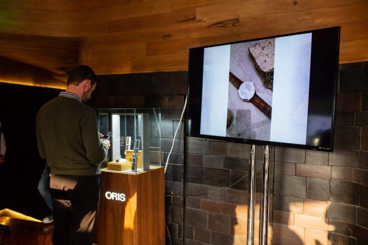 -Persona viendo el reloj Oris Artix junto a una pantalla con una imagen del reloj