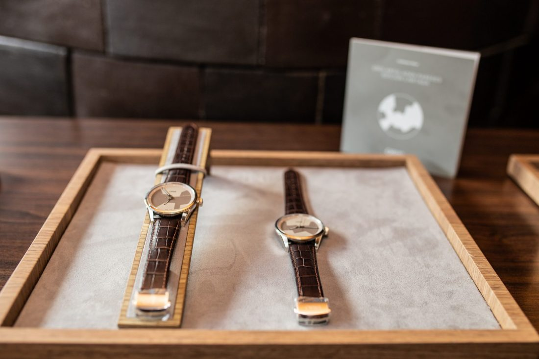 Reloj Oris Artix con detalles plateados y correas en color café sobre una caja de madera