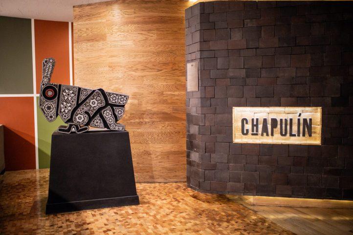 Entrada al restaurante Chapulín con la figura de un chapulín sobre una plataforma café de madera