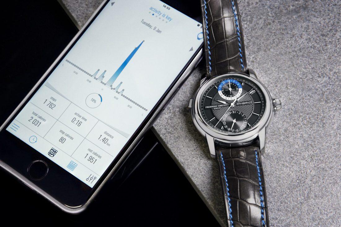 Reloj en color negro con detalles plateados y azules junto a un celular