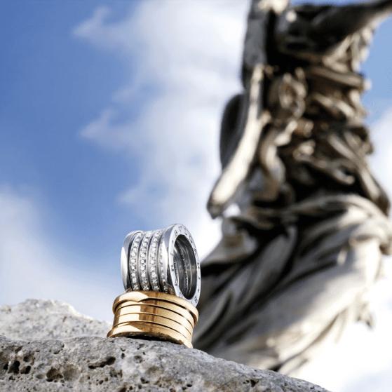 Anillo en color plateado y dorado sobre una piedra con una estatua al fondo