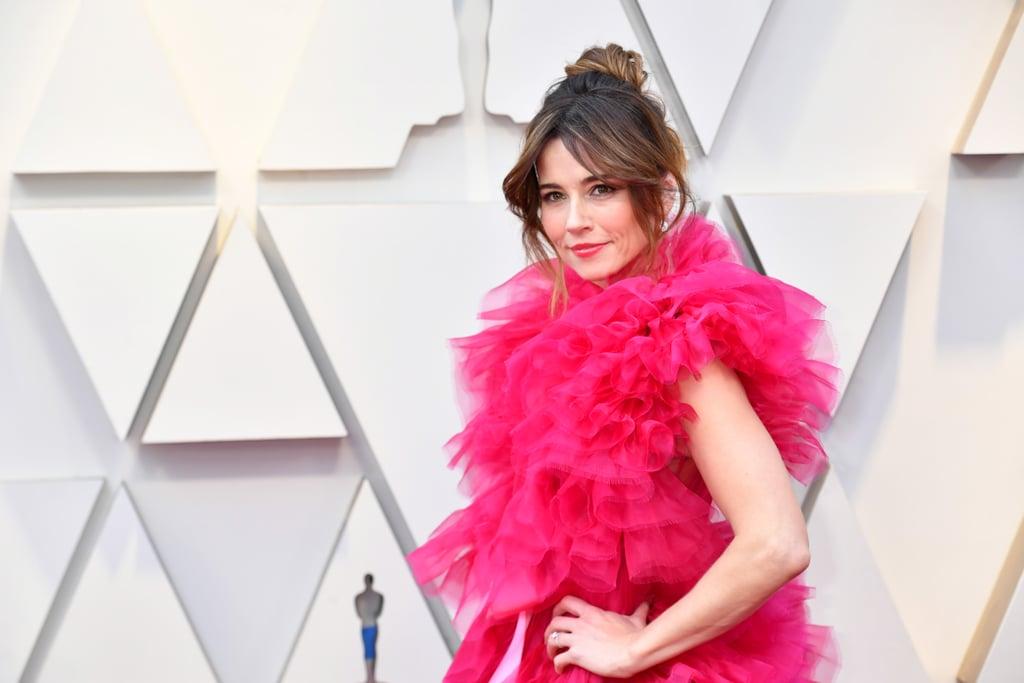 Linda Cardellini con vestido rosa con aretes y anillo de diamantes