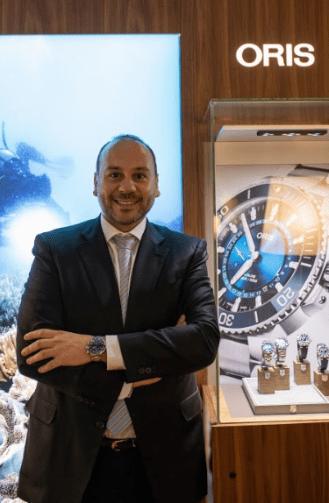 Alberto Rodriguez con traje negro cruzado de manos a lado de una vitrina con relojes oris