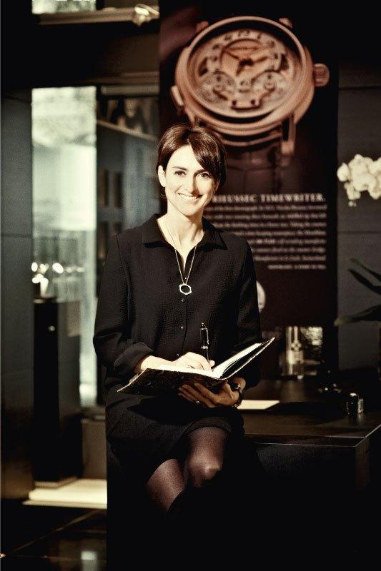 Delphine Favier con una libreta y pluma en las manos sentada en el escritorio de su oficina